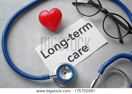 Stethoscope and paper sheet with text LONG-TERM CARE on table
