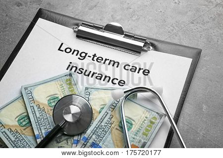 Text LONG-TERM CARE INSURANCE on clipboard with stethoscope and dollars closeup