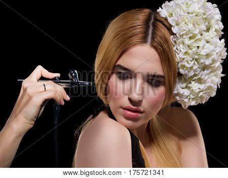 portrait of a beautiful young blonde woman on a dark background. there is hand with aerograph making an airbrush make up. copy space.
