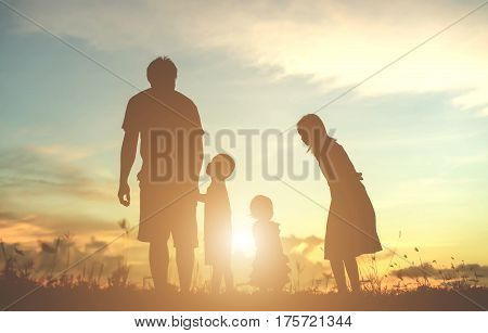 Silhouette of a family comprising a father, mother and two children happy family the sunset.Concept of friendly