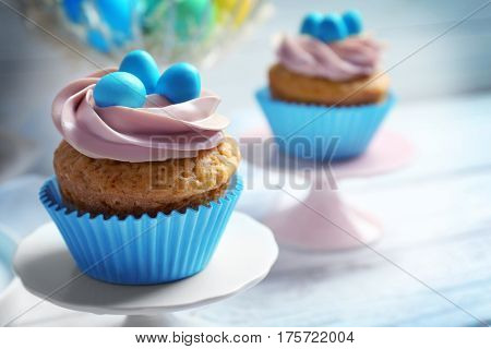 Cake stand with delicious Easter cupcake on white wooden table