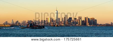 Panoramic Sunset of Lower Manhattan and New York City Harbor with Financial District skyscrapers and passing tugboat