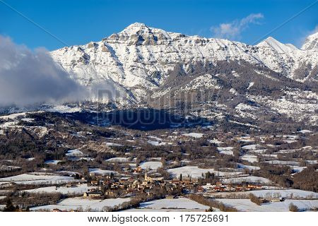 The village of Saint-Julien-en-Champsaur and the Queyrel Peak mountain in winter. Hautes Alpes Southern French Alps France