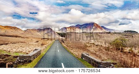 Landscape with road and mountains on a cloudy day in Ireland