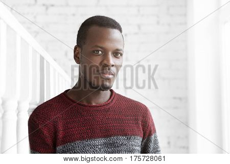 Attractive Young African American Male Dressed Casually Looking At Camera With Dreamy Expression, De