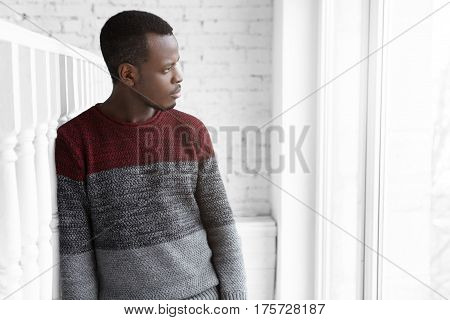 Serious And Thoughtful Young Dark-skinned Male Architect Dressed Casually, Leaning Shoulder On White