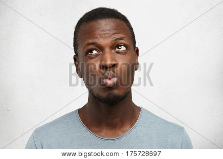 I Don't Know. Headshot Of Doubtful African American Male Wearing Casual Grey Shirt, Pouting Lips And