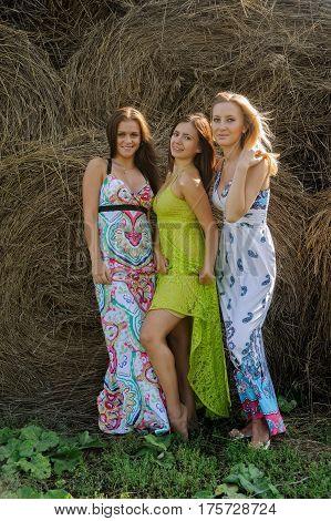 Three attractive flirting women standing on hay stacks