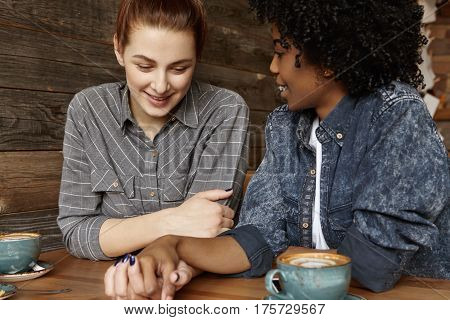 Happy Interracial Lesbian Female Couple Relaxing At Cafe During Lunch: Attractive Woman With Ginger