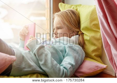 Indoor Shot Of Adorable European Female Kid Having Serious And Concentrated Look While Using Mobile