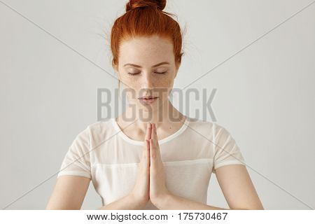 Gorgeous Young Caucasian Female Wearing Her Ginger Hair In Bun, Holding Hands In Namaste Or Prayer,