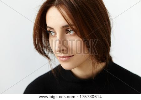 Studio Shot Of Attractive European Model With Dark Hair Having Dreamy And Thoughtful Expression On H