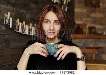 Cute Student Girl With Blue Nails Holding Mug, Enjoying Fresh Cappuccino At Coffee Shop After Sleepl