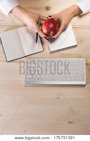 Business woman in an office holding red apple - Clipping Path
