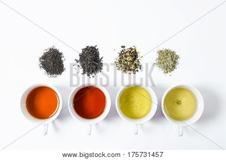 Collection of different teas in cups with tea leaves on a white background.