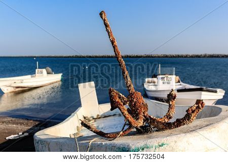 old rusty anchor on fishing boat. Fishing port