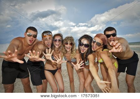 Joyful team of friends having fun at the beach