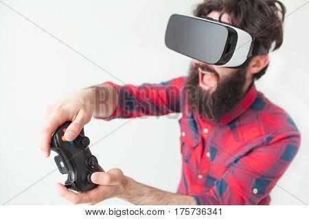 Bearded cheerful man wearing VR headset and holding a gamepad. Horizontal studio shot.