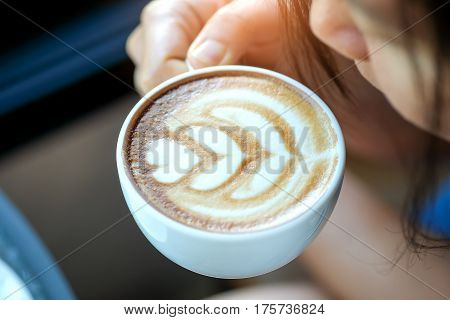 Woman raising heart late coffee cup to drink near the mouth.
