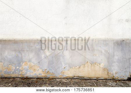 Old weathered white plaster wall and a ground