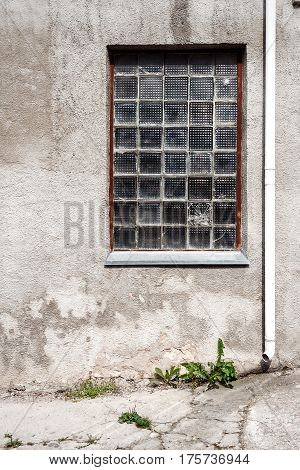Concrete wall with glass block window and ground. Architecture background
