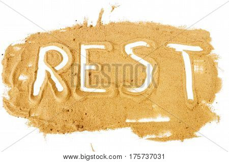 Word REST written on pile of yellow sand isolated on white background selective focus at center