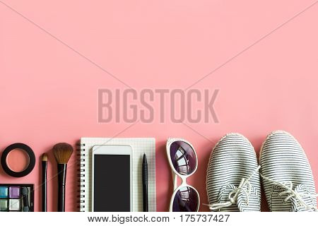 Woman stuff makeup cellphone and accessories isolated on pink background with copy space Fashion concept