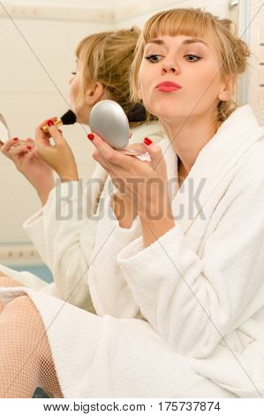 beautiful woman using mascara brush in bathroom