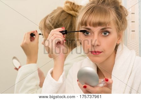 attractive woman using mascara eyeliner close up