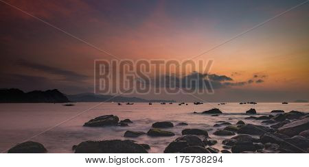 A fiery orange morning sky looking out over the south China sea in Vung Lam Bay Vietnam. With a rock covered coastline and fishing boat silhouettes coming and going.