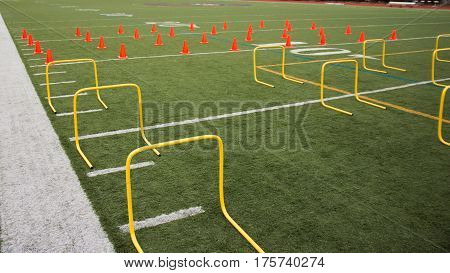 A green turf field is set up with orange cones and yellow hurdles for speed work