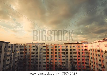 Color image of some flats in a block at sunset.