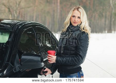 Woman With A Red Cup Of Hot Drink Keeps The Car Door Handle
