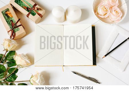Opened empty diary, pen, vintage tray, candles, roses on white background. Flat Lay, top view, mockup