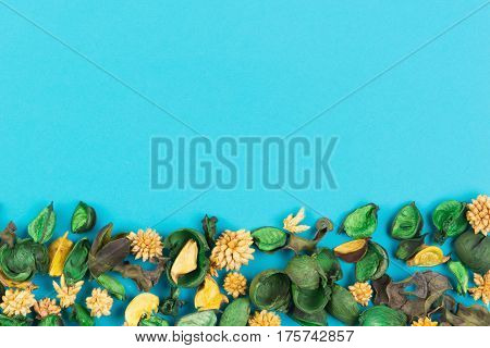 Dried flowers composition on blue background. Frame made of dried flowers and leaves. Top view, flat lay. Copy space for text