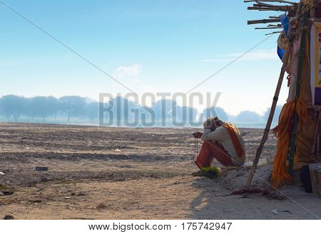 The hermit a sadhu sits meditating on the opposite of the Varanasi banks of the Holy river Ganges