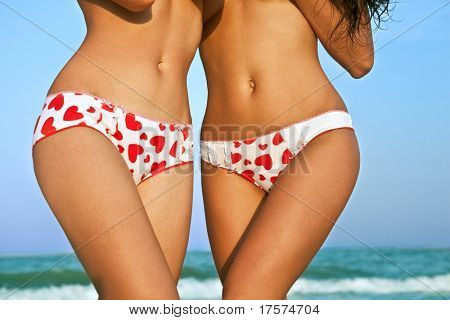 Sexy female bodies in pants with hearts against the sea coast