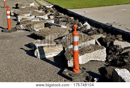 Orange cones warn of a street and curb repair construction project where large chunks of concrete are broken into chunks