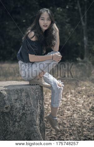 portrait of beautiful asian younger woman model sitting on tree stump