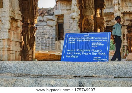 Hampi, India - November 19, 2012: Ancient Indian architecture for restoration. Sign about the restoration work in the courtyard of Vittala Temple in Hampi, Karnataka, India.