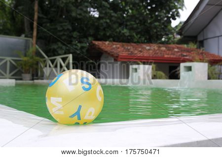 Child's yellow ball floating in blue pool