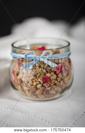 Cereal in jar with blue ribbon on white tablecloth.