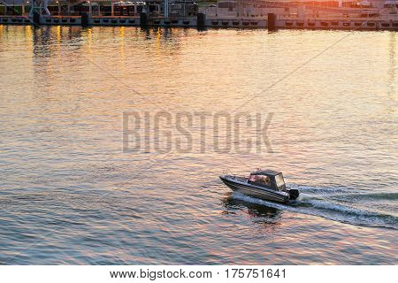 Small motor boat approaching to marine passenger-cargo harbor of Tallinn. Motor leaves strong wave behind boat. Sun reflected from calm surface of water. Evening view of sea bay at sunset. Estonia