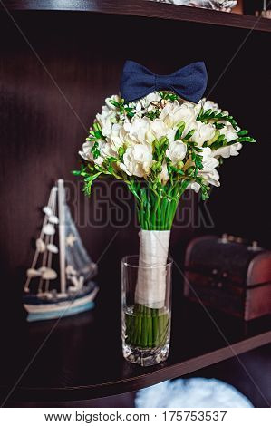 dark blue bow tie on a luxury bridal bouquet of white flowers on a shelf. Souvenirs from the sea