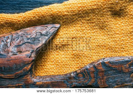 Combination of brown and black wood and yellow knitted textures. Close-up direct view