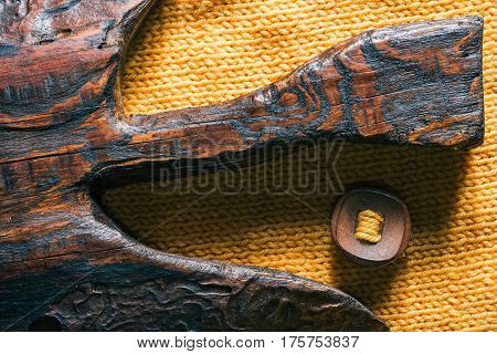 Combination of curved board of brown wood and yellow knitted textures with wood button. Close-up direct view