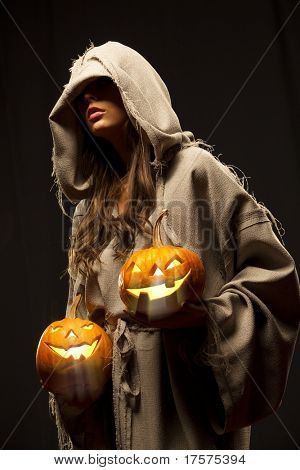 woman in robe wrapped around her head holding halloween pumpkins