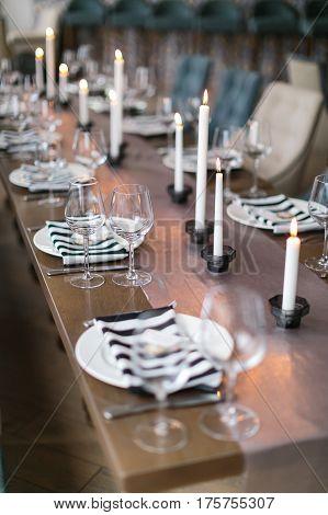 Wedding decor. Wedding interior. Festive table decor. Restaurant interior. The burning candles on a table.