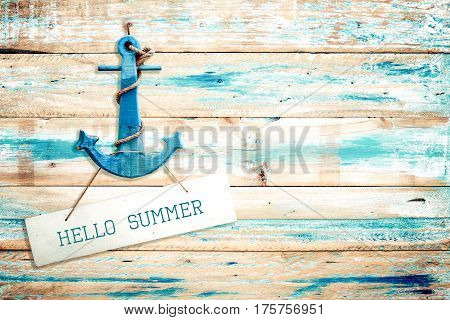 Vintage Hello summer sign hanging with anchor on old wooden blue paint background. vintage wood texture from beach in summer.