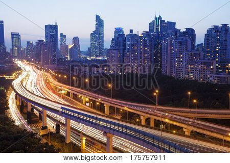 night scene of busy elevated road in midtown of modern city